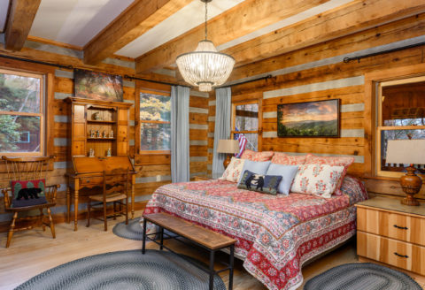 Cozy Cabin Update to the Master Bedroom complete with log beams and hardwood flooring