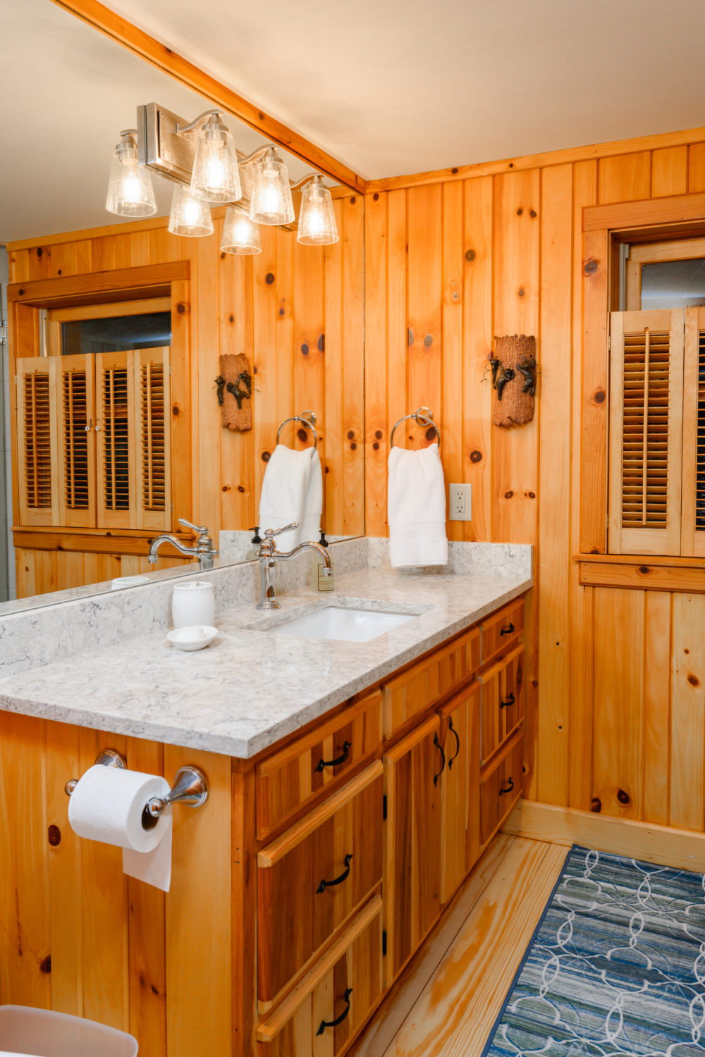 Pine wood paneling creates a rustic feel for this renovated bathroom in the cozy cabin update