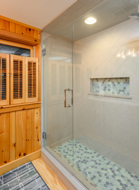 Glass enclosed shower uses a herringbone tile pattern for the wall but a blue mosaic pebble for the floor