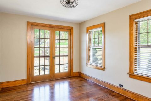Tall floor moldings encase this rich dining room area that opens up onto the porch