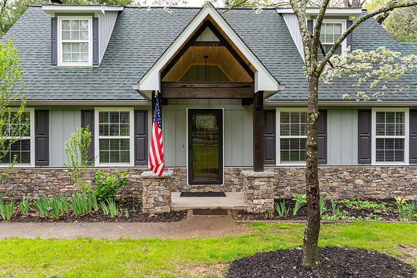 Beautiful front porch features a vaulted entry and stunning rock work