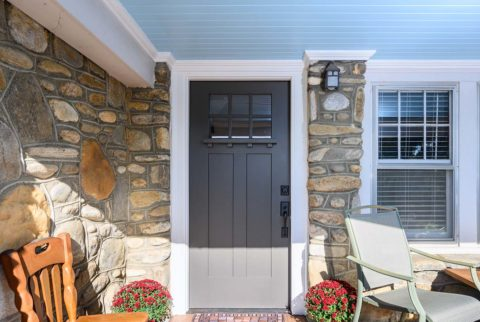 Craftsman style front door complements this stone bungalow