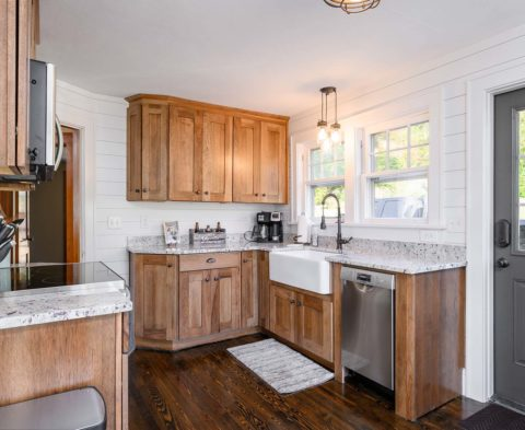 Farmhouse sink with granite countertops and oak cabinets complete this modern rustic style kitchen