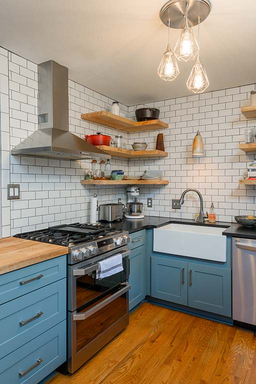 Farmhouse style sink with modern countertops and a stainless steel gas stove