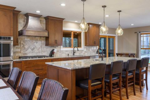 Pendant lights over a long center island complements this kitchen style