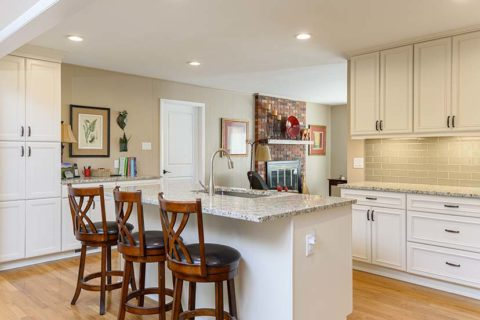 Kitchen remodel with granite countertops, white cabinets, and stainless steel appliances