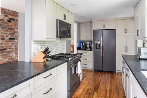 Semper Fi Custom Remodeling Kitchens - Oak hardwood floors standout against the white cabinetry and dark stainless steel appliances